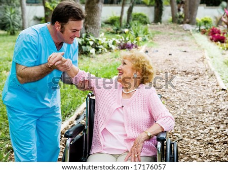 Beautiful disabled senior woman receiving physical therapy in an outdoor setting. - stock photo