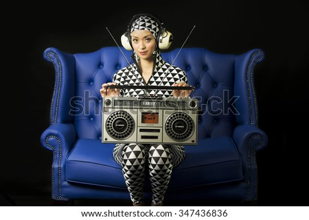 beautiful disco woman in black and white suit posing with vintage ghettoblaster - stock photo