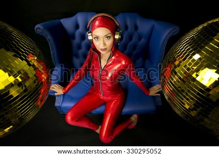 beautiful disco woman in red cat suit posing in blue chair - stock photo