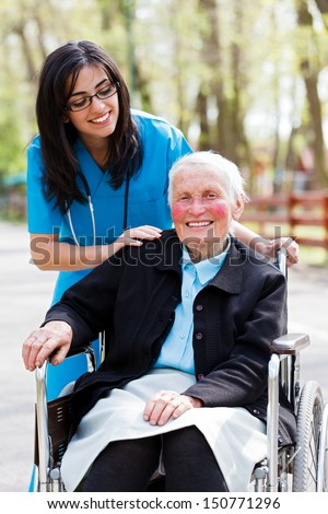 Beautiful doctor, nurse in blue coat walking a kind elderly lady in wheelchair in park.