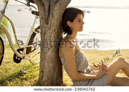 Beautiful dormant woman in love waiting under an olive's tree - stock photo