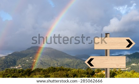 Beautiful double rainbow over landscape with signposts. Life metaphor sun and rain or trekking etc. - stock photo