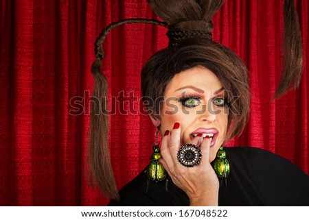 Beautiful drag queen staring and biting nails - stock photo