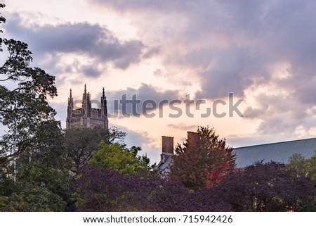 beautiful dramatic cloudy sky at sunset hidden castle tower behind colorful trees in autumn colors