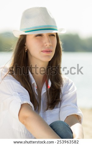 Beautiful dreaming girl at the beach. Thoughtful caucasian woman at summer vacation - stock photo