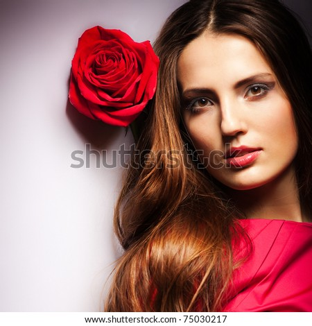 Beautiful dreaming girl with red roses in her hair - stock photo