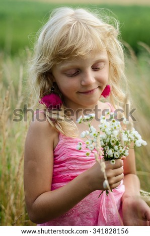 beautiful dreamlike little girl with long blond hair and bunch of flowers in the meadow portrait - stock photo