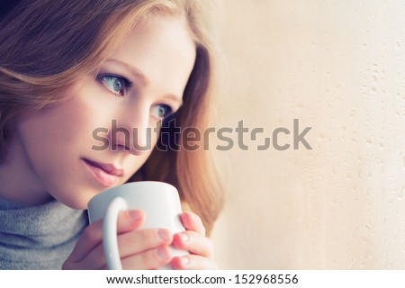 beautiful dreamy girl with a cup of hot drink coffee at the window - stock photo