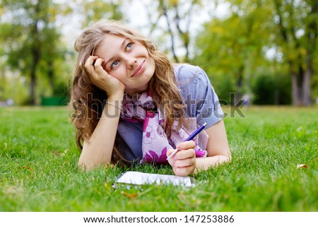 Beautiful dreamy teen girl lying on grass in park with pen and notebook - stock photo