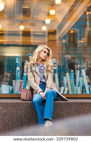 Beautiful dreamy woman relaxing after walking in urban setting during free time, attractive girl with trendy look posing outdoors, alluring female waiting for her friends while sitting on a shop sill  - stock photo