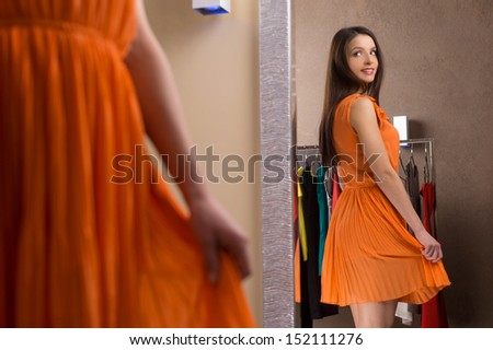 Beautiful dress. Attractive young woman in orange dress looking at the mirror and smiling - stock photo