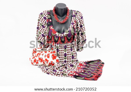 Beautiful dress on mannequin with matching accessories. Elegant dress on tailor's dummy with matching colorful purse and red necklace - stock photo