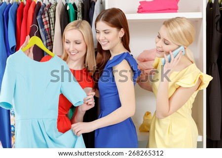 Beautiful dress. Three female friends doing shopping together while two of them trying a new blue dress and the other talks over the phone - stock photo