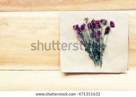 Beautiful dry flowers on old paper on wooden background