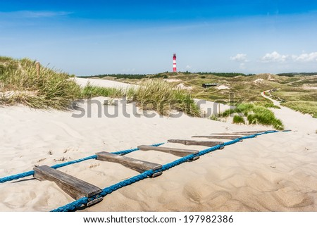 Beautiful dune landscape with traditional lighthouse on the island of Amrum at North Sea, Schleswig-Holstein, Germany - stock photo