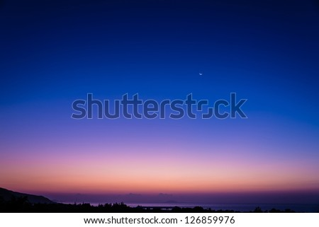 beautiful early morning dawn twilight with moon and star at the sea - stock photo