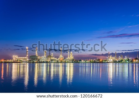 beautiful early morning twilight at petroleum refinery along the river - stock photo