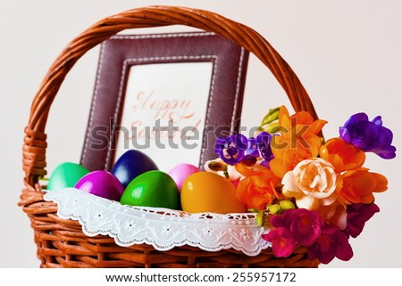 beautiful easter eggs and flowers freesia in wicker basket with frame inscription text
