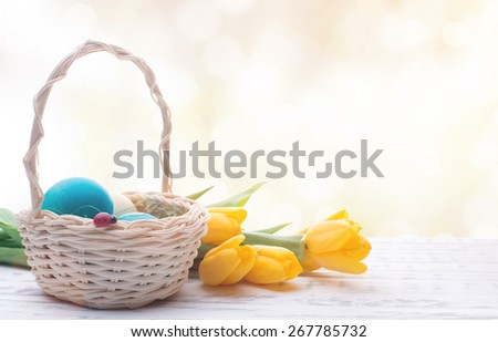Beautiful Easter eggs in a basket. Delicate yellow spring tulips. Spring Easter holidays. Wooden board rustic. Beautiful light background - stock photo