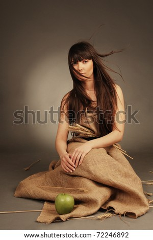 Beautiful eco woman with wheat ears and green apple. - stock photo