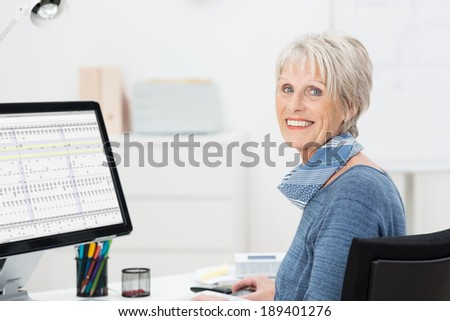 Beautiful elderly businesswoman sitting at her desk working on a spreadsheet on a large desktop monitor turning to smile at the camera - stock photo