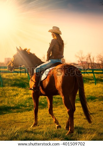 Beautiful elegance back woman cowgirl, riding a horse. Clothed blue jeans, brown leather jacket and hat. Has slim sport body. Portrait nature. People and animals. Equestrian. Amazing sunset. - stock photo