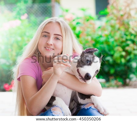 Beautiful elegance girl, has smiling face, blonde white long hair, dressed pink t-shirt. Playing with  puppy stafford.  Nature portrait. Close up.