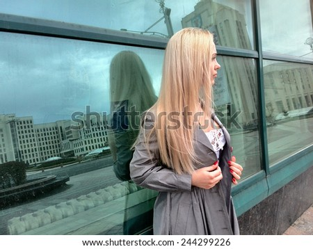 Beautiful elegant blonde woman in autumn clothes standing near a modern building. Blond young sexy attractive woman in gray coat and white dress posing near a glass street city window. - stock photo