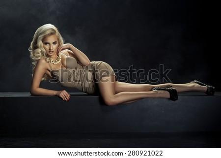 Beautiful elegant blonde woman posing in lingerie, lying,  - stock photo