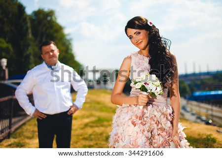 Beautiful elegant bride in pink dress and handsome groom - stock photo
