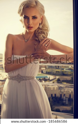 beautiful elegant  bride with blond hair posing at the balcony with panoramic view