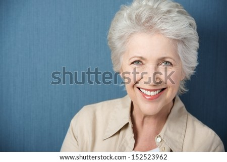 Beautiful elegant elderly lady with a lively smile looking directly at the camera while posing against a green background with copyspace - stock photo
