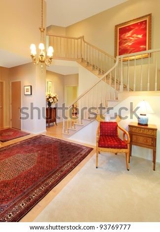 Beautiful elegant entrance, living room and stair case. - stock photo