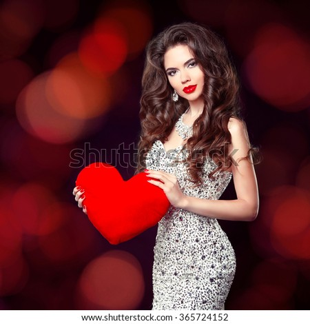 Beautiful elegant girl with red heart gift for Valentines Day. Brunette slim woman in luxury dress isolated on holiday bokeh background.  - stock photo