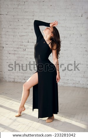 Beautiful elegant gymnastics athlete girl wearing long black dress, posing in studio. Over white brick wall background in studio - stock photo