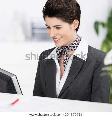 Beautiful elegant hotel receptionist or secretary wearing a stylish neck scarf sitting working at her computer with a smile - stock photo