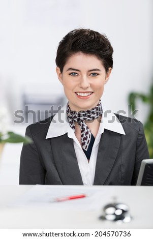 Beautiful elegant hotel receptionist with a lovely friendly smile in a stylish outfit with a scarf and a short modern haircut - stock photo