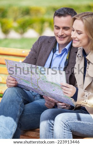 beautiful elegant mid age couple resting outdoors. man holding map and talking to blond woman - stock photo