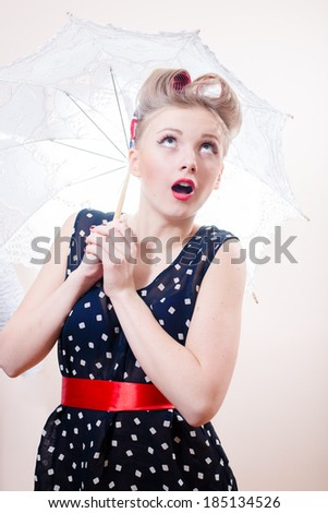 Beautiful elegant pinup woman with umbrella looking up surprised - stock photo