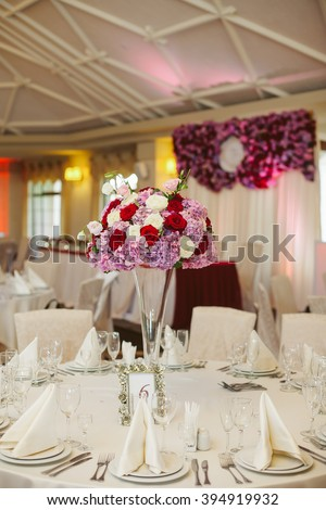 Beautiful elegant wedding reception table arrangement, purple flowers - stock photo