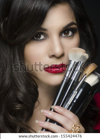 Beautiful elegant woman holding makeup brushes