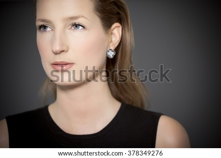 Beautiful elegant woman in black top over dark grey background.