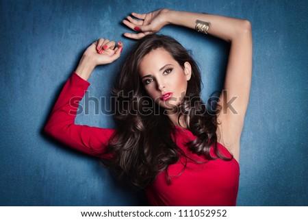 beautiful elegant woman in red dress on blue wall studio shot - stock photo
