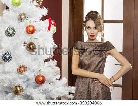 beautiful elegant woman , in shining golden dress ready for christmas party , near a white tree with decoration. she is looking in camera - stock photo