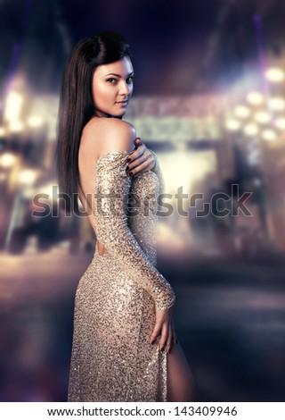 Beautiful elegant woman standing at the night street - stock photo