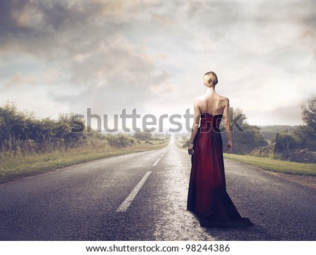 Beautiful elegant woman walking on a country road