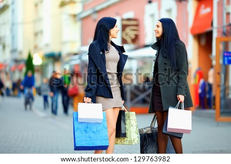 beautiful elegant women walking the crowded city street with shopping bags