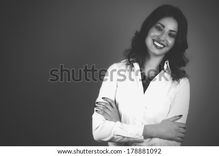 Beautiful elegant young lady with a confident smile and folded hands. Black & white version.