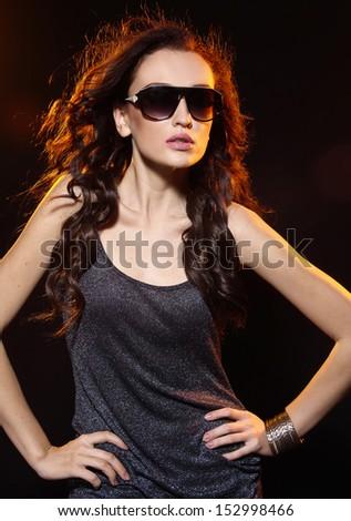 Beautiful elegant young woman in sunglasses wearing black dress - stock photo