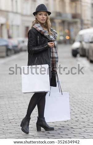 beautiful elegant young woman walking on the street , with hat and scarf ready for shopping sales